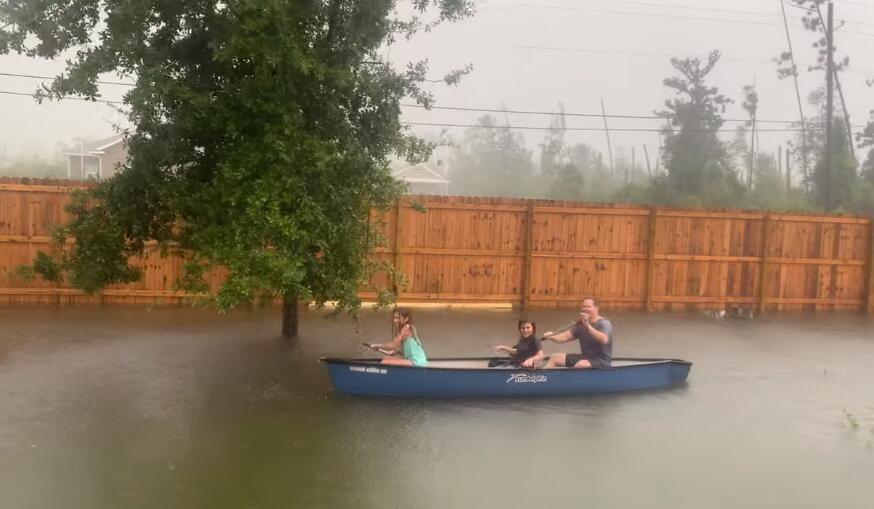 佛罗里达州一名父亲带着子女在被暴雨淹没的后院划船